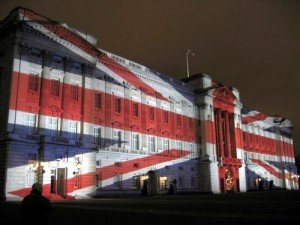 Buckingham Palace with a Union Jack projected onto it.